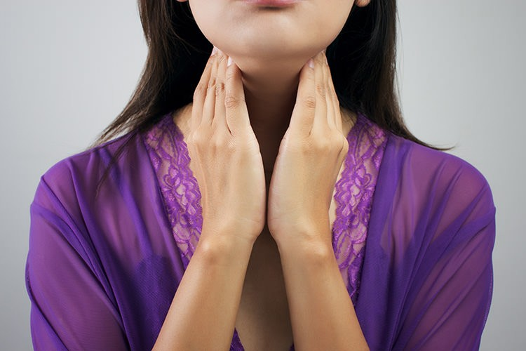 Woman with Thyroid Disease holding her throat
