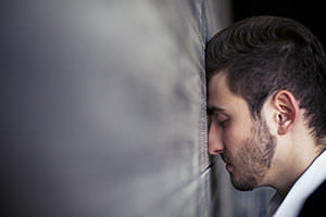 Man with head up against a wall