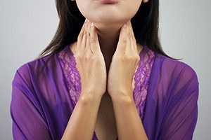 Woman with hands on her neck